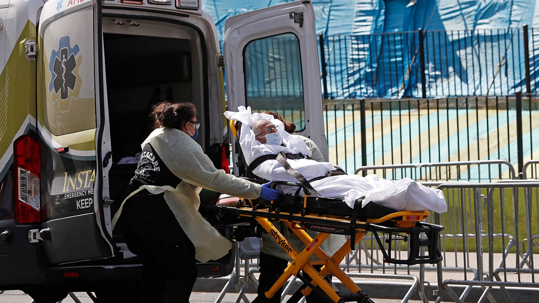 A patient is transferred from Elmhurst Hospital Center to a waiting ambulance during the current coronavirus outbreak, Tuesday, April 7, 2020, in New York. (AP Photo/Kathy Willens)