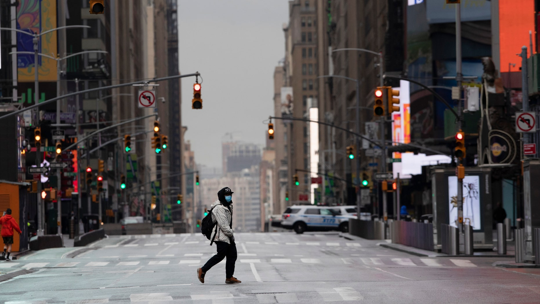A man wearing a mask crosses the street in a quiet Times Square, Thursday, April 9, 2020, during the coronavirus epidemic. (AP Photo/Mark Lennihan)