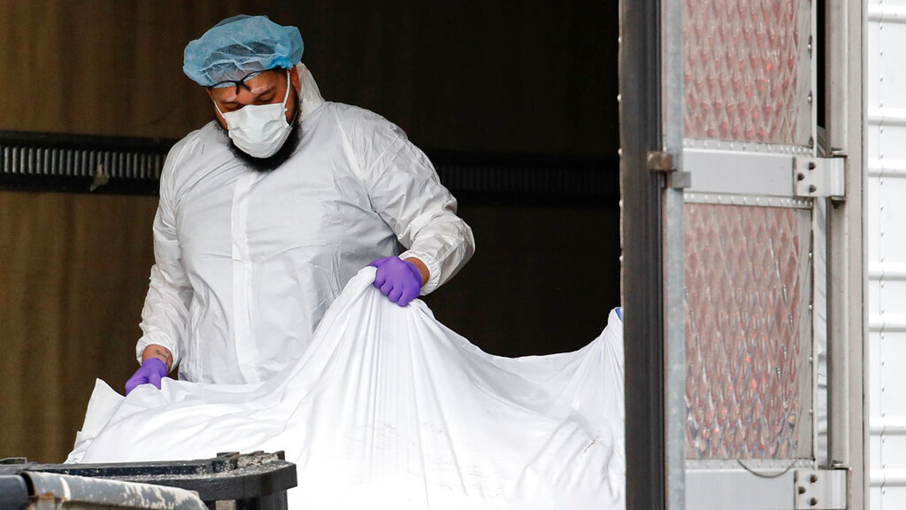 A body wrapped in plastic is loaded onto a refrigerated container truck used as a temporary morgue by medical workers wearing personal protective equipment due to COVID-19 concerns. (AP Photo/John Minchillo)