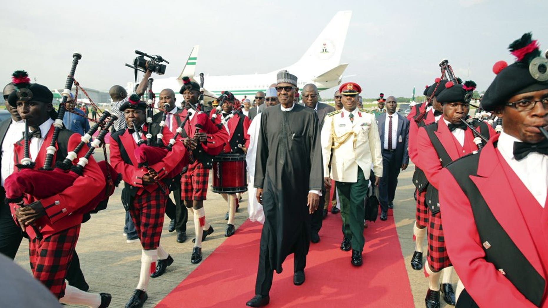 In this Aug. 19, 2017, file photo released by the Nigeria State House, Nigeria's President Muhammadu Buhari, center, walks upon his arrival at the airport in Abuja, Nigeria, after returning from more than three months in London for medical treatment. The coronavirus pandemic could narrow one gaping inequality in Africa, where some heads of state and other elite jet off to Europe or Asia for health care unavailable in their nations but as global travel restrictions tighten, they might have to take their chances at home. (Sunday Aghaeze/Nigeria State House via AP, File)
