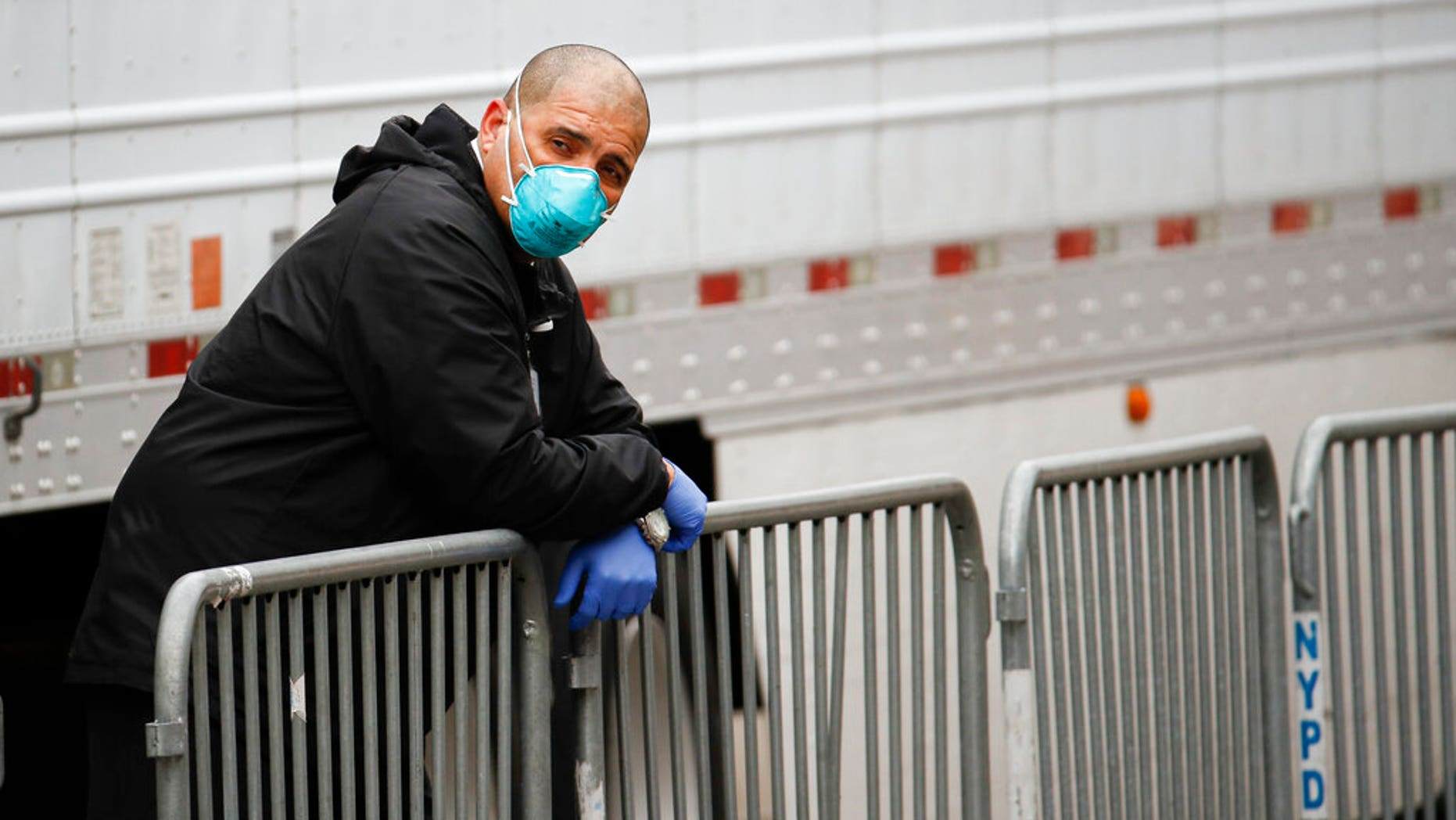 A medical worker wearing personal protective equipment due to COVID-19 concerns rests beside a refrigerated container truck functioning as a makeshift morgue. (AP Photo/John Minchillo)
