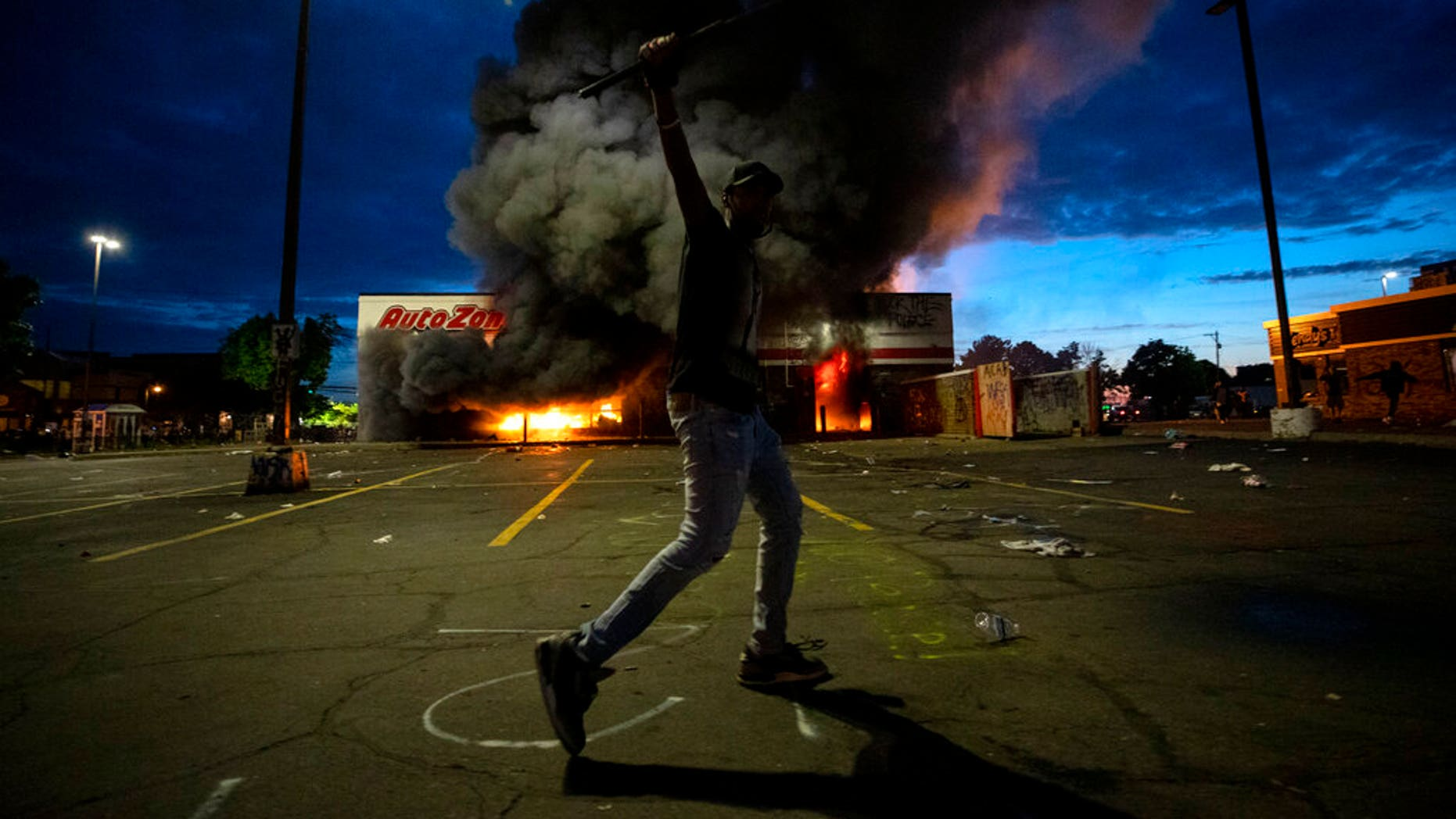 A man poses for a photo in the parking lot of an AutoZone store in flames, while protesters hold a rally for George Floyd in Minneapolis on Wednesday, May 27, 2020.(Carlos Gonzalez/Star Tribune via AP)