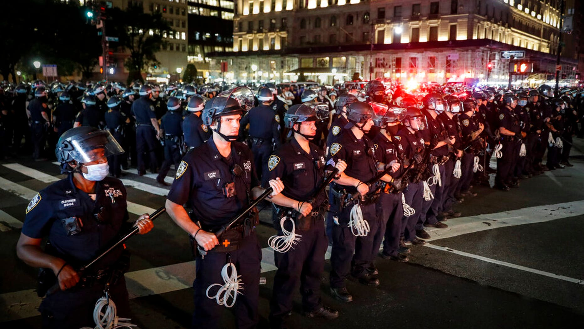 New York Police Department officers stand in formation after arresting multiple protesters marching after curfew on Fifth Avenue. (AP Photo/John Minchillo)