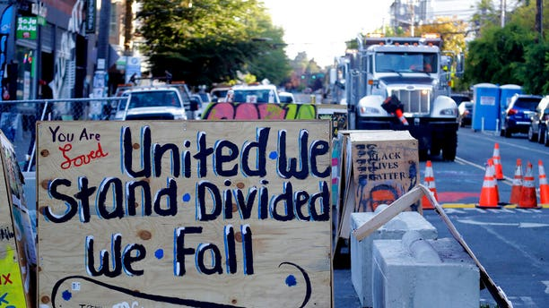 """A sign on a barricade reads """"United we stand divided we fall,"""" as a truck and other heavy equipment from the Seattle Department of Transportation is staged at the CHOP (Capitol Hill Occupied Protest) zone in Seattle, Friday, June 26, 2020."""