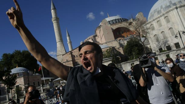 People chant slogans following Turkey's Council of State's decision, outside the Byzantine-era Hagia Sophia, one of Istanbul's main tourist attractions in the historic Sultanahmet district of Istanbul, Friday, July 10, 2020.