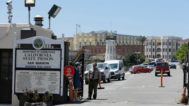 A Department of Corrections officer guards the main entryway leading into San Quentin State Prison in San Quentin, Calif. Corrections officials said Friday that up to 8,000 state prison inmates could be released in an effort to prevent the spread of the coronavirus in correctional facilities. (AP Photo/Eric Risberg, File)