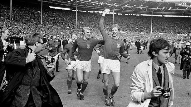 England's Jack Charlton, right, holds the Jules Rimet trophy aloft as he parades it around Wembley Stadium with teammate Bobby Moore following their 4-2 win over West Germany, July 30, 1966. (Associated Press)
