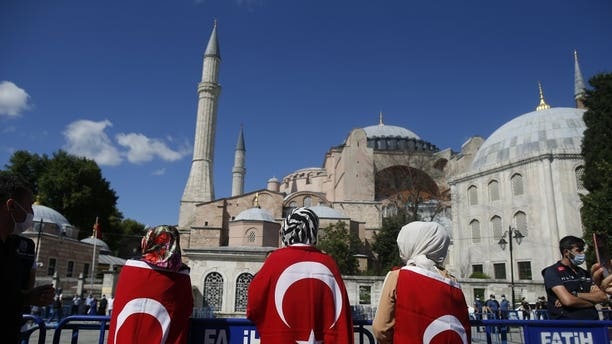 People, draped in Turkish flags, gather outside the Byzantine-era Hagia Sophia, one of Istanbul's main tourist attractions in the historic Sultanahmet district of Istanbul, following Turkey's Council of State's decision, Friday, July 10, 2020.