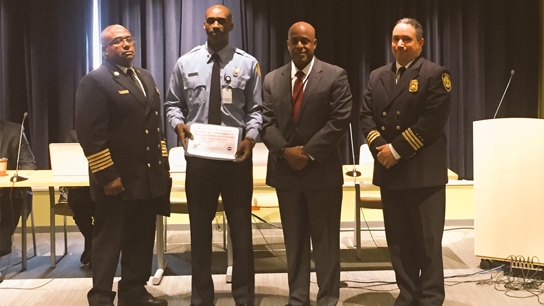 Detroit Firefighter Sivad Johnson holds plaque given to him in 2016 for saving the life of an unconscious man.