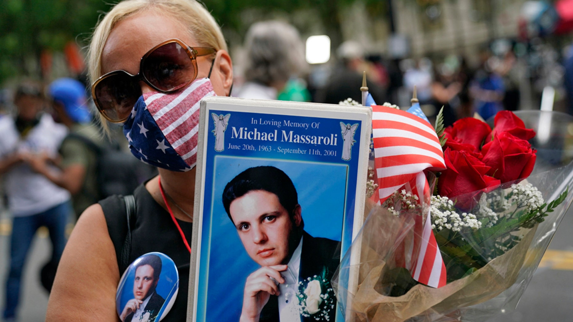 Diane Massaroli holds flowers, flags and a photo of her husband Michael Massaroli who died during the Sept. 11, 2001, attacks at the World Trade Center. (AP Photo/Mark Lennihan)