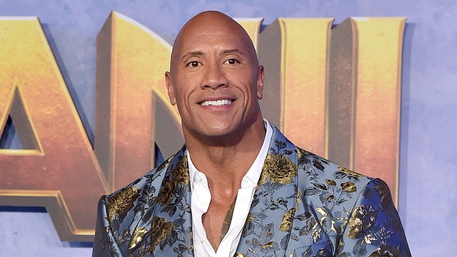 Dwayne 'The Rock' Johnson reacts to seeing himself blown up as fanny pack balloon in Thanksgiving parade