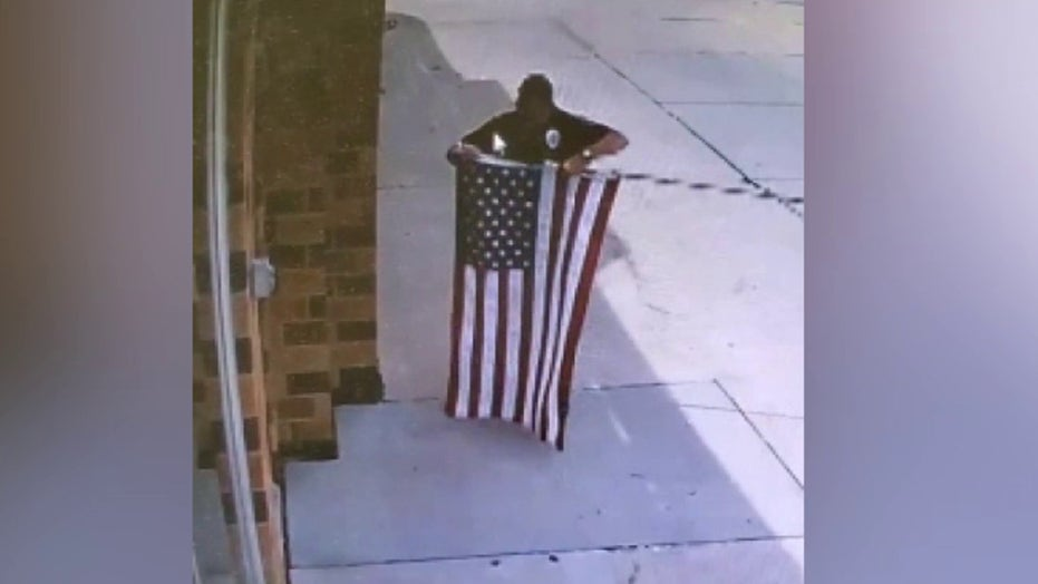 Raw Video: Police officer stops to fix fallen flag outside Nebraska business
