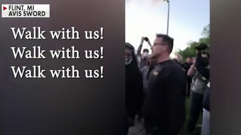 Michigan sheriff walks with protesters in effort to repair community relations