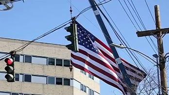 Tree service hangs giant US flag, 'thank you' sign at hospitals during coronavirus crisis