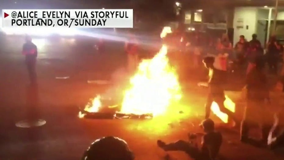 Portland demonstrators gather near police precinct, set fires