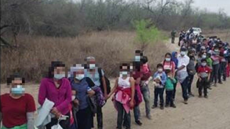 Federal agents apprehending large groups of migrants crossing the US-Mexico border