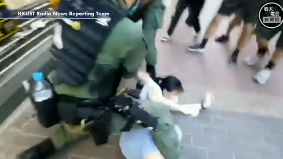 Police in Hong Kong tackle young girl to ground