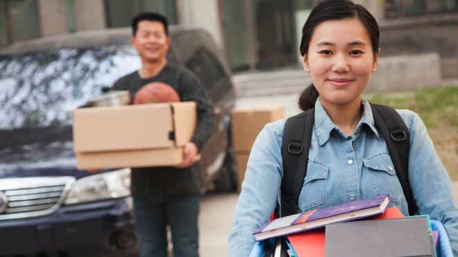 Female student holding packed box move away for college