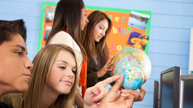 High school students look at globe and learn in classroom education