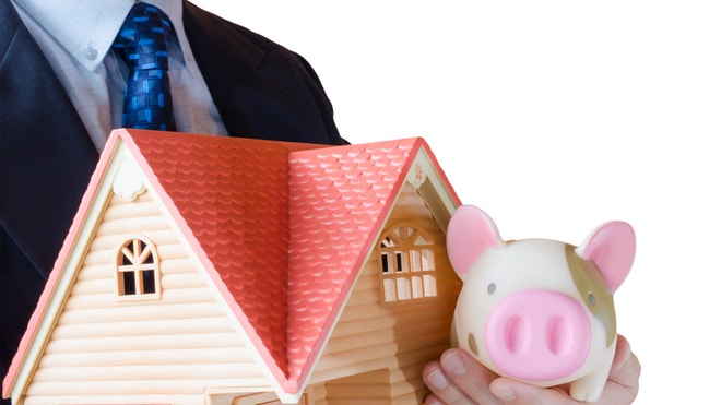 Man holds doll house and penny bank for mortgage, borrowing