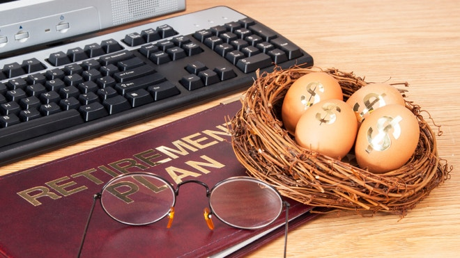 Retirement IRA, 401k, pension plan book and nest egg with computer
