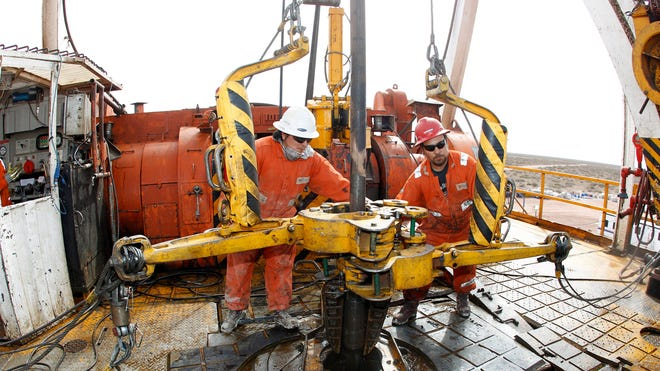 Oil Workers Operate Drill