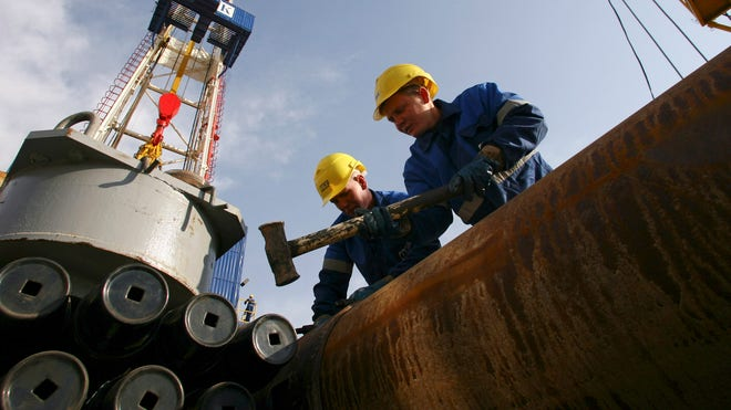 Oil Workers Look Into Gas Field
