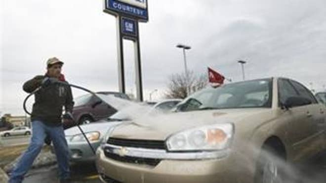 An employee at a General Motors dealership washes down cars (AP Photo).