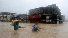 Torrential monsoon rains worsened by a tropical storm flooded large swathes of the Philippine capital and nearby provinces Friday, leaving at least three people dead and displacing tens of thousands just days after the region was drenched by a typhoon.