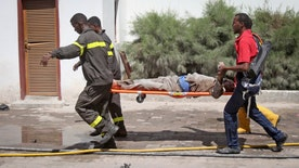 Government officials were meeting at the Central Hotel in Somalia's capital when an Islamic extremist rammed an explosives-laden vehicle into the hotel gate, and another went in and blew himself up, killing at least  people on Friday, officials said.