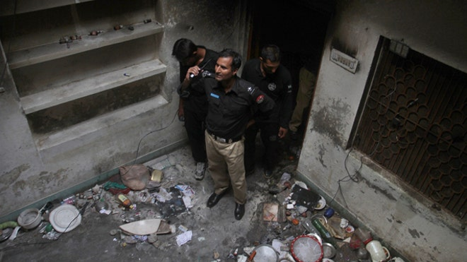 A Pakistani mob burned down several homes belonging to the minority Ahmadi sect in the country's east, killing a woman and her two granddaughters in riots following rumors about blasphemous postings on Facebook, police said Monday.