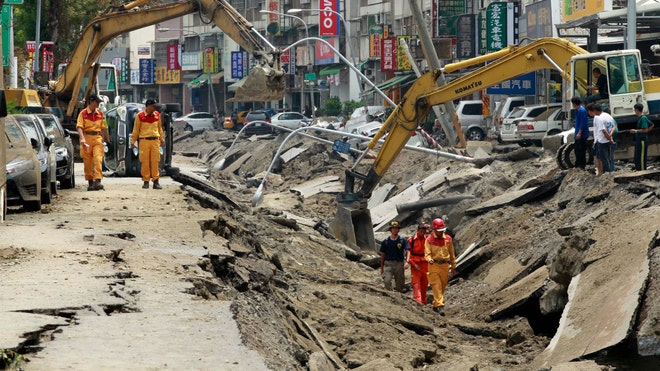 Heavy machinery pulled vehicles from huge trenches gouged by explosions along an underground pipeline in Taiwan's second-largest city that killed at least  people and injured .
