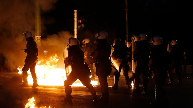 Rioters hurled petrol bombs at police who responded with tear gas during an anti-austerity demonstration outside parliament Wednesday, as Greek lawmakers began debating contentious measures needed to start negotiations on a new bailout and avoid financial collapse.