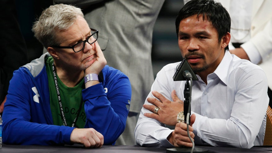 FILE - In this May 2, 2015 photo, trainer Freddie Roach, left, listens as Manny Pacquiao answers questions during a press conference following his welterweight title fight against Floyd Mayweather Jr. in Las Vegas. (AP Photo/John Locher)