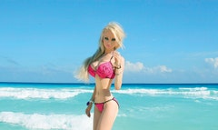 The surgically enhanced life-life Barbie posted a new video early Thursday, which shows her workout routine and features scenes of her frolicking on the beach in barely there ensembles.