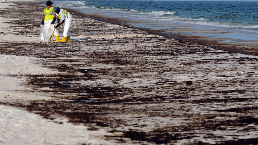 Crews clean up oil from the Deepwater Horizon spill at Pensacola Beach