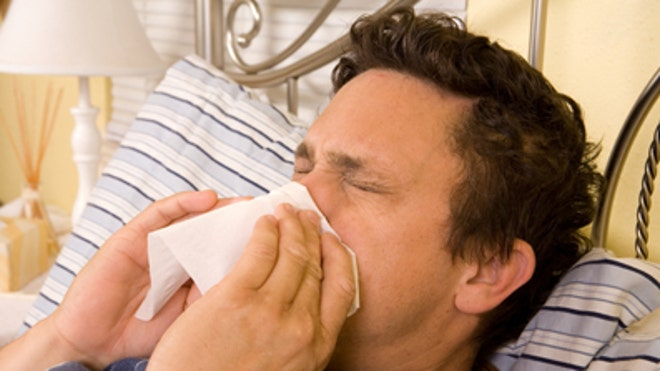 Man sick in bed with flu iStock