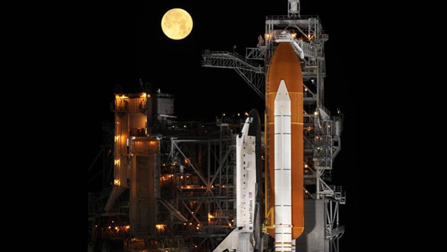 Behind the shuttle, a nearly full moon sets