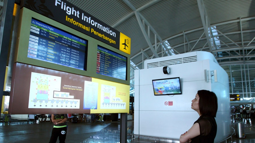 July 10, 2015: A traveler checks the status of flights at Bali's international airport, Indonesia. (AP Photo/Firdia Lisnawati)