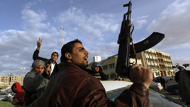 Libyan protester w gun screams against Qaddafi