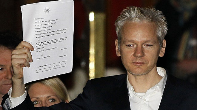 Assange, freed, holds up paper in London