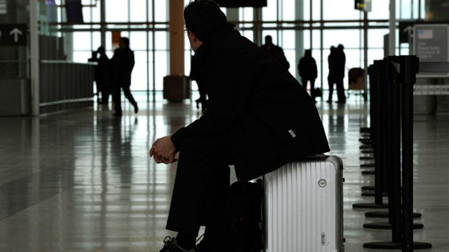Traveler Sits on Suitcase