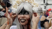 Hundreds of Brazilians dressed as zombies dragged their rotting limbs on Wednesday while groaning and playfully lurching at tourists along Rio de Janeiro's Copacabana Beach.