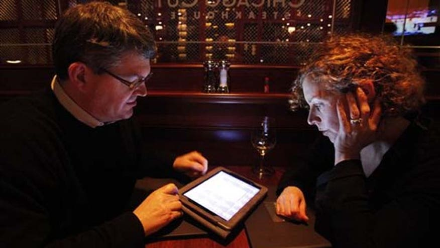 Couple hunched over ipad