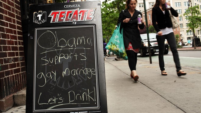 Patrons walk by the Stonewall Inn, a historic gay bar in Greenwich Village, ...