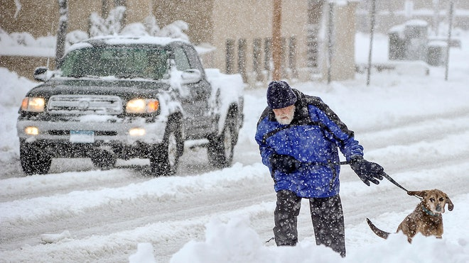 mike gregg trudges through the snow thursday morning in austin minn to