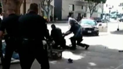 Three Los Angeles police officers shot and killed a man on the city's Skid Row during a struggle over one of the officers' guns, authorities said late Sunday.
