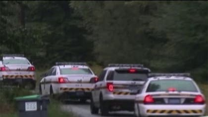 Investigators on Sunday returned to scour the woods across from a state police barracks where two troopers were ambushed, leaving one fatally shot and another critically wounded.