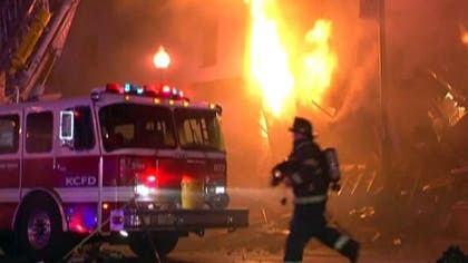Two firefighters who saved two residents from a burning apartment building in Kansas City were killed Monday night after suffering injuries when the structure collapsed around them, authorities said.