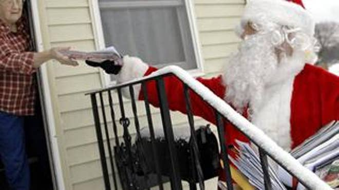 A postal worker dressed as Santa Claus delivers the mail. Dec. 24, 2008